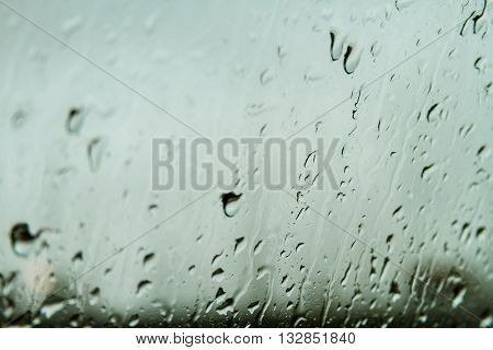 Water drops on a glass after rain with background cloudy day
