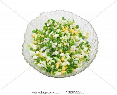 Top view to spring salad with chopped green onions and chopped boiled eggs in a glass salad bowl on a light background