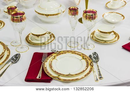 Fragment of table setting with tableware cutlery and a glass decorated with golden and red ornament