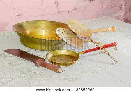Some subjects of a older kitchen utensils consisting of two various copper frying pans and slotted spoons large kitchen knife on table with old tablecloth against background of the brickwork