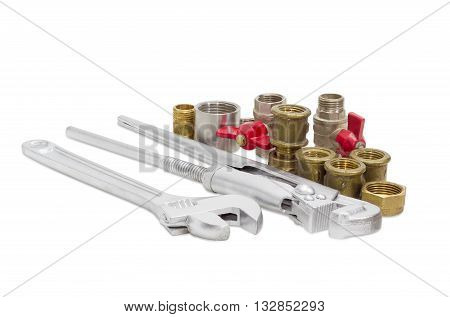 Plumber wrench adjustable wrench with silvery coating and several different steel and brass plumbing components on a light background