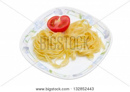 Boiled noodles tagliatelle and half fresh tomato on dish on a light background