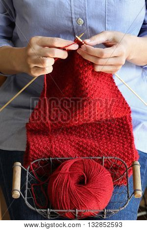 woman hands knitting red woolen scarf