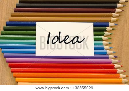 Idea text concept and colored pencil on wooden background