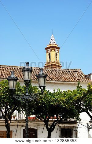 Lamppost with church spire to the rear in the Plaza las Flores Estepona Malaga Province Andalucia Spain Western Europe.
