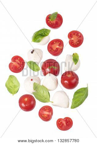 Round camembert cheese with cherry tomatoes and basil on a white.