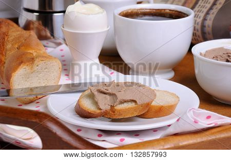 A slice of toast spread with liver pate for breakfast and a cup of coffee on a tray