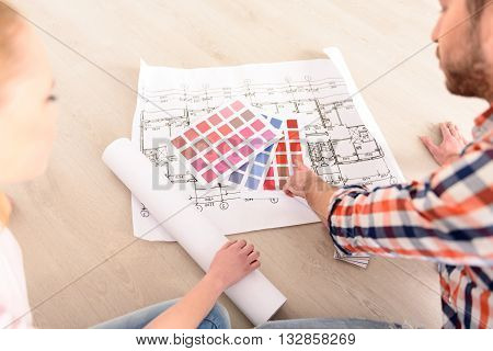 I think it most appropriate color. Yong man and woman determine color for repair of their apartment using color palette, sitting on floor