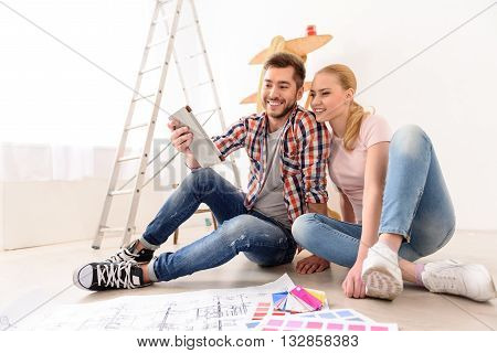 So many variants. Young couple in love moving in new apartment, sitting on the floor, planning to redecorate their new home, using tablet