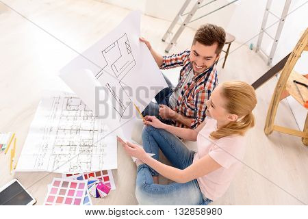 Planning always interesting. Top view of smiling couple having fun deciding on paint colour swatch for new home apartment