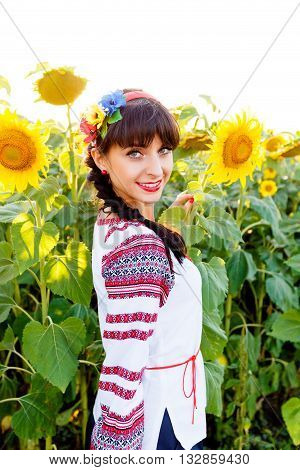 Beautiful smiling woman in national ukrainian blouse embrodery looking to camera on a sunflower field on sunset backlight