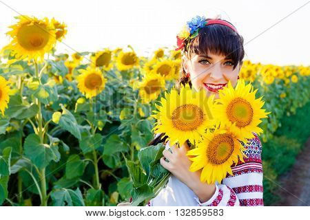 Beautiful smiling woman in national ukrainian blouse embrodery holding three sunflowers on a plant at sunset backlight.