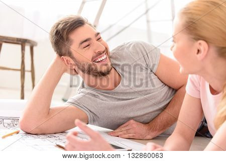 So happy of such changes. Happy young guy smiling and looking at her girlfriend, discussing new idea for apartment, looking each other