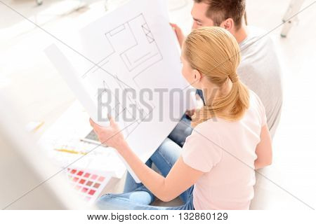 We have plan. Young couple planning decoration when moving home sitting on the floor, discussing plan of house