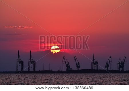 Silhouette of cranes at the harbor at sunset