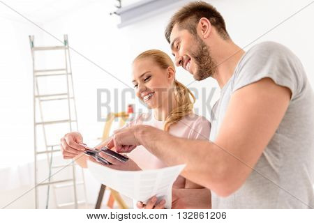 Always hard to choose. Happy smiling couple making repairs in their apartment and picks up color of walls, using palette of colors