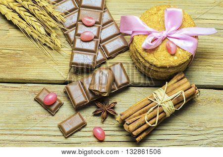 Still life with a delicious chocolate placed with corn biscuits,cinnamon and pink candies on arustic wooden table,top view