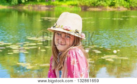 Portrait of a cute little girl in a hat on the lake shore