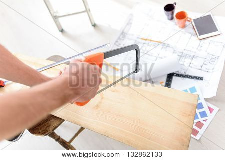 It will not be difficult. Close up of man holding saw in his hand and sawing wooden board