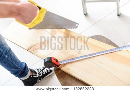 This takes a steady hand. Close up of male hands cutting parquet floor board with saw