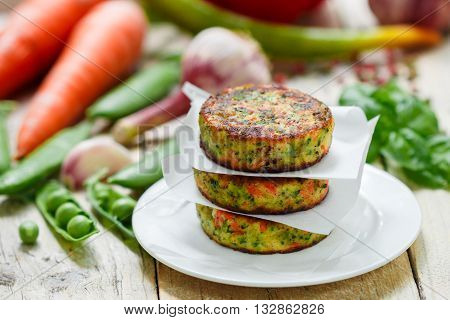 Healthy vegetarian patties made from potatoes carrots onions green peas herbs and spices. Selective focus