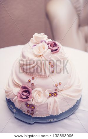 three-tiered beautiful wedding cake with roses on the table.