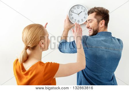 We all done on time. Smiling couple hanging wall clock on white wall looking each other, isolated on white background