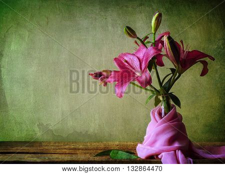 Still life with pink lilies flower and silky scarf on a rustic wooden table
