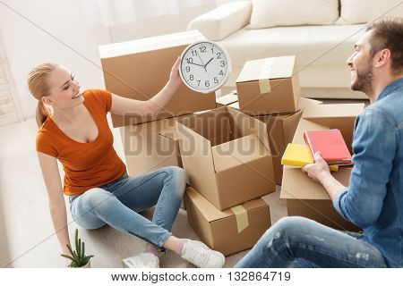 Packing is fun when you do it together. Happy smiling girl gets out of cardboard box wall clock and showing for guy