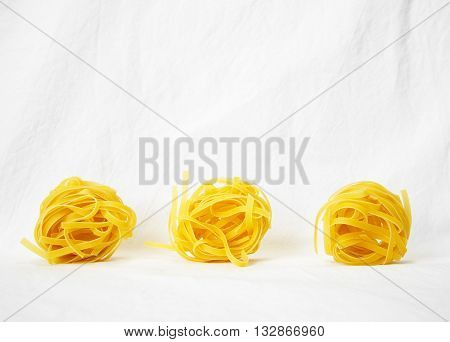 three raw tagliatelle pasta on white background