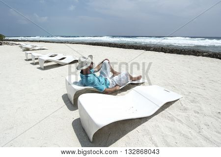 Man in hat from the sunon a sun lounger in the beach