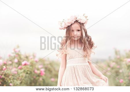 Beautiful baby girl 3-4 year old walking in rose garden with wreath of flowers outdoors. Looking at camera. Childhood.