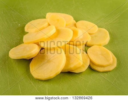 Pile of sliced peeled potatoe on green used plastic board, simple food preparation illustration, vegetarian dieting, still life with center composition