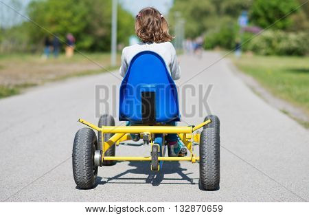 Little girl riding on pedal karting. Back view