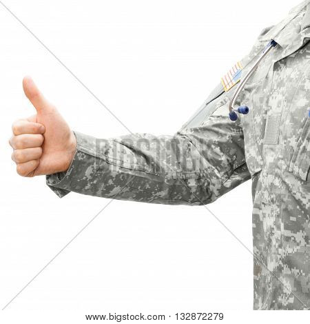 Close up studio shot of US Army doctor holding thumb up