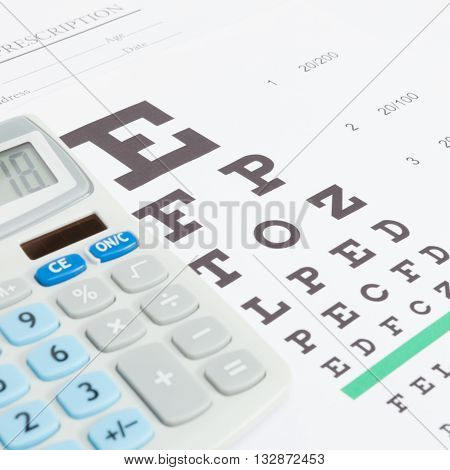 Eyesight test table and medical prescription form with neat calculator over it - close up studio shot