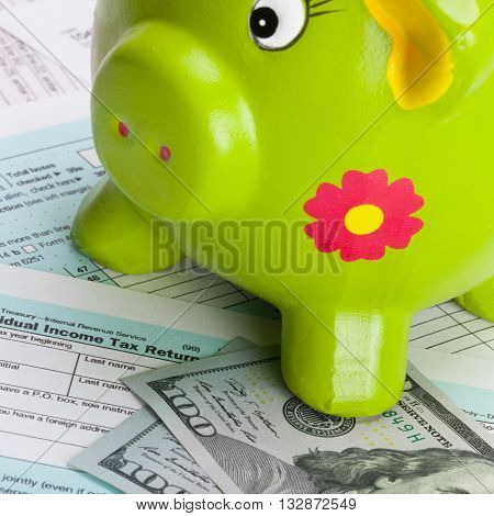 Hundred Dollars Banknote And Piggy Bank Over Us Tax Form