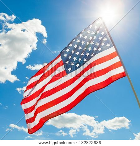 American Flag Waving In Blue Sky With Sun Behind It