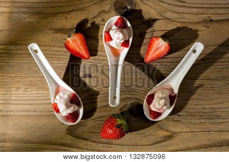 Mascarpone cream and strawberries seen from above on wooden background