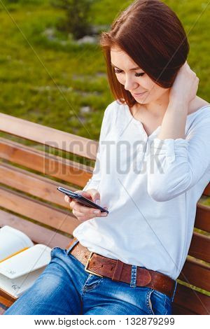Young woman sitting on a bench in the park, talking on the phone
