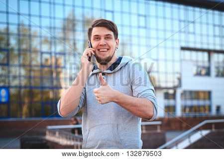 Portrait of a young man in casual clothes with a phone on the background of the business center. The informal business, free business concept