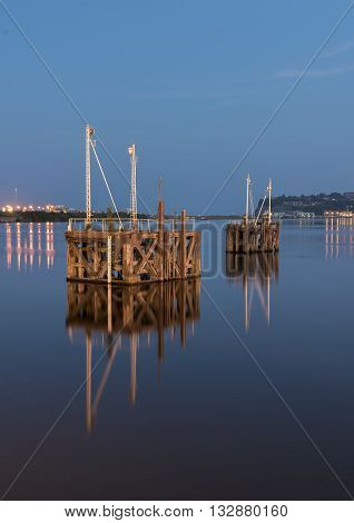 Two wooden boat jetty's, in the middle of a harbor, at night, reflecting in the very calm water of Cardiff Bay