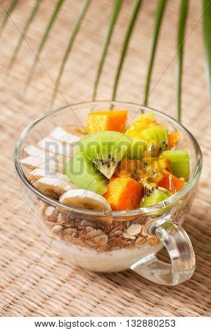 Dietary breakfast. Muesli yoghurt tropical fruits: mango kiwi pineapple passion fruit in cup on a straw background