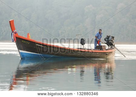Suratthani Thailand - April 14 2015: Fisherman sailing wooden long tail boat on water in forest dam of Ratchaprapa in Suratthani southern province in Thailand.