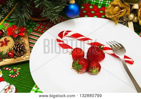 New Year Christmas Christmas tablecloth with a pattern of Santa Claus CHRISTMAS HOLLY gifts a fork with a plate of fresh red berries and strawberries and candy in Christmas red and white stripes and the background color of the flower golden candlestick