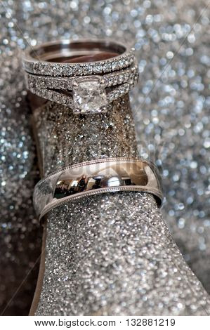 Wedding rings sparkling against the wedding shoe heel.