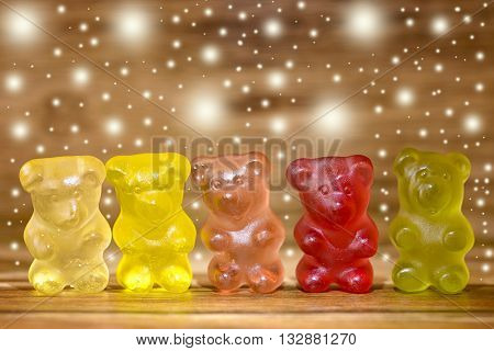 multicolored gummy bear and glitter on wood