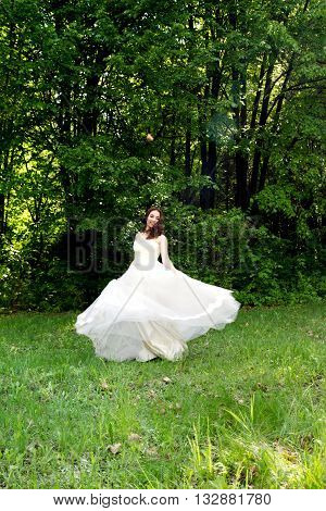 Beautiful and happy bride turned in a forest glade