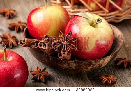 Apples with spices: cinnamon star anise on a wooden background