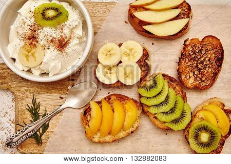 Various fruit sandwiches and ricotta with banana kiwi apple apricot. Healthy organic and vegan breakfast on wooden background. Rustic style